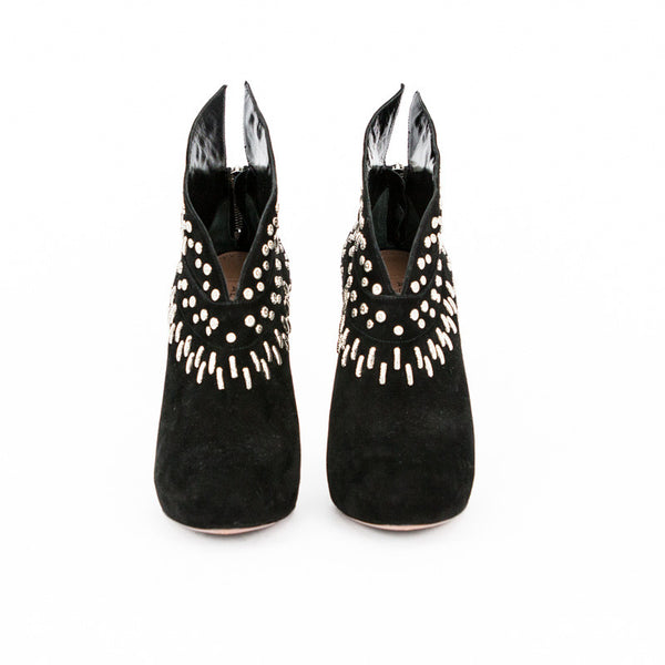 Alaia black suede stiletto booties with silver tone stud accents, round toe, covered heel, and zip closure.