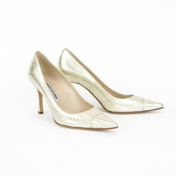 Manolo Blahnik metallic gold pumps with brogue detail, pointed toes, and covered heels.