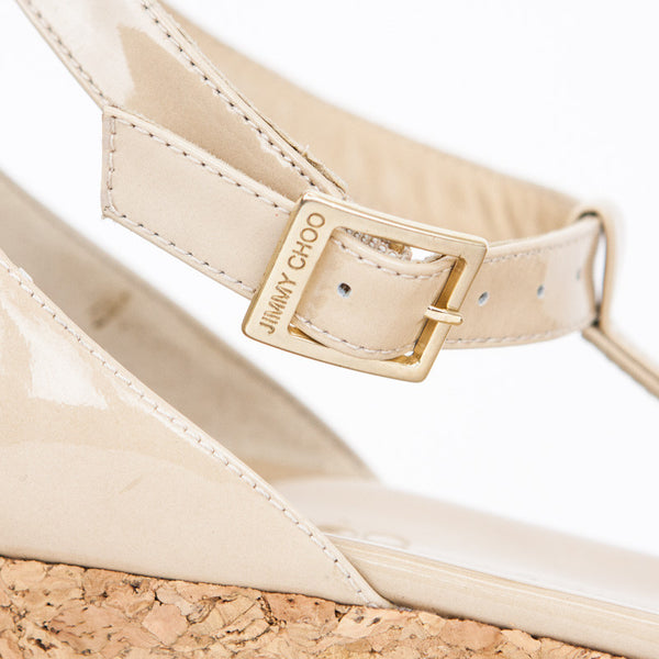 Jimmy Choo beige patent leather t- strap cork wedges with open toes and adjustable ankle straps with buckle closures.