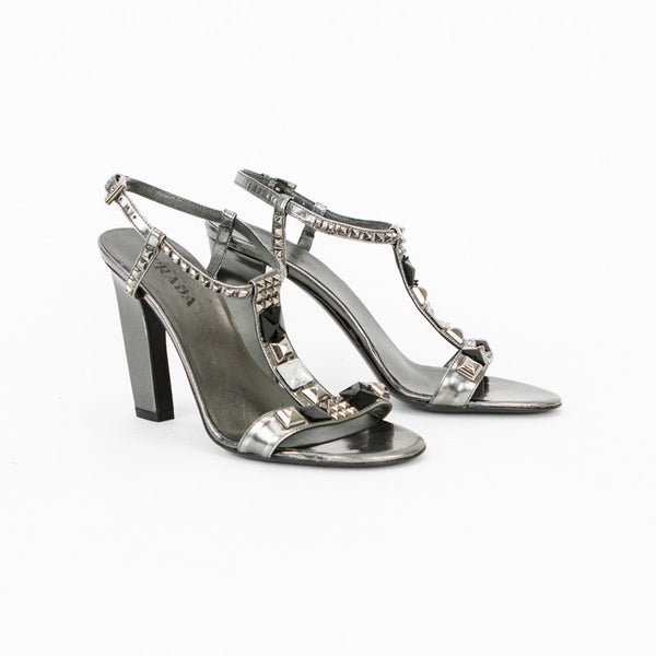Prada metallic gunmetal t-strap sandals with stud accents, adjustable ankle straps, and covered heels.