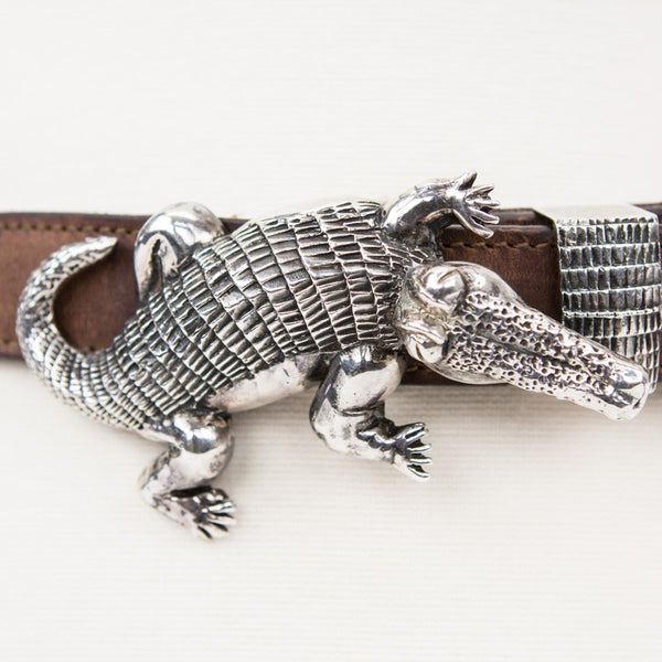 Brown leather belt with arrow lacing detail on back and sterling silver detachable alligator buckle and loop.
