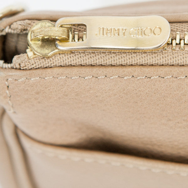 Jimmy Choo beige leather pochette with exterior front slide pocket, top zip closure, and brass tone hardware.