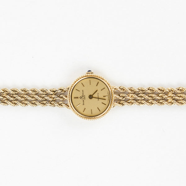 Baume & Mercier 14k gold triple rope chain watch with snap lock closure and stick dial.