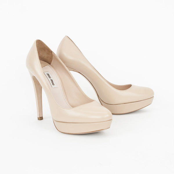 Miu Miu beige leather platform pumps with almond toes and covered heels.