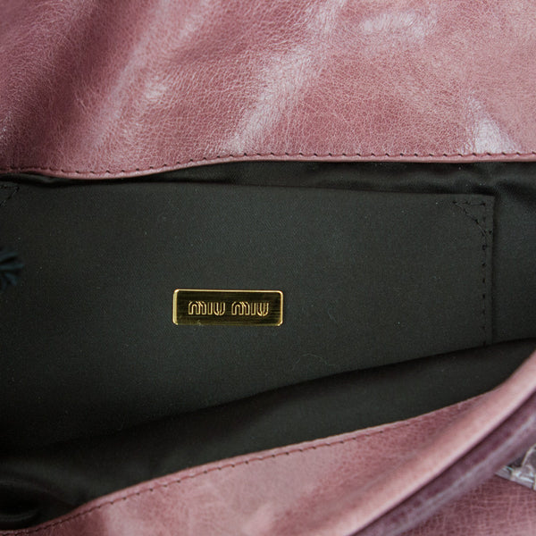 Miu Miu leather fold over clutch with dragonfly appliqué, gold tone handle, and snap closure.