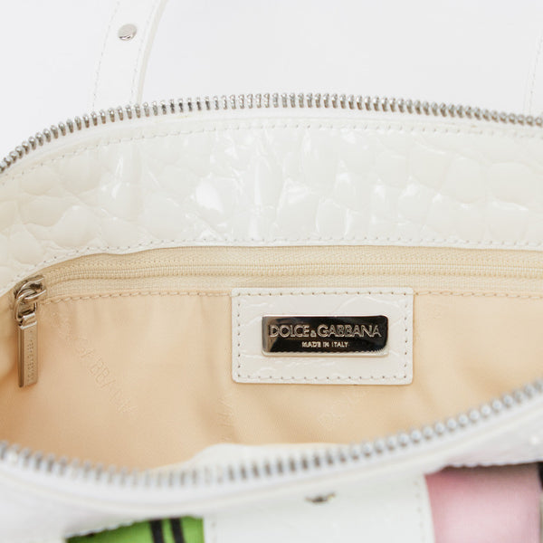 Dolce Gabbana pink, green, and white cloth baguette handbag with white patent leather trim embellished with Swarovski crystals. Designer name plate interior pocket