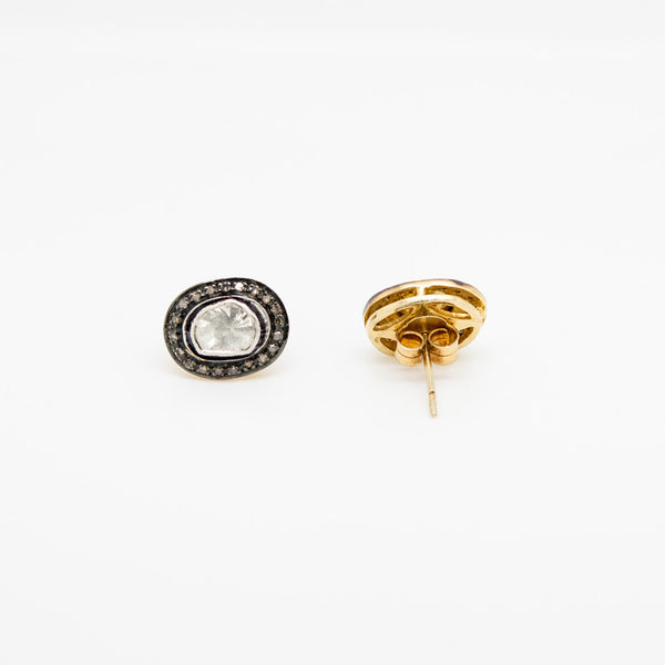 Oval stud earrings with a central indian rough cut diamond surrounded by pave diamonds mounted on gold tone sterling silver.