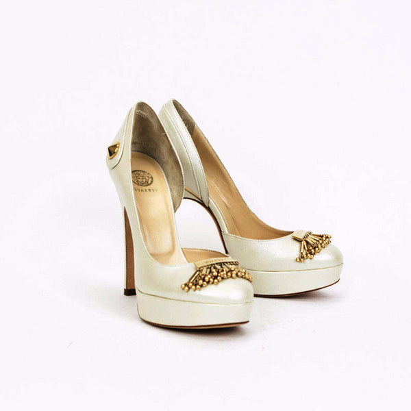 This Versace shoe has gold tone on the back of the heel with a gold tone stud on the outside of the heel.