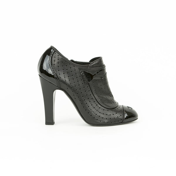 Chanel black bootie with perforated leather, patent leather covered heels and toes, with logo stitched on cap toes.