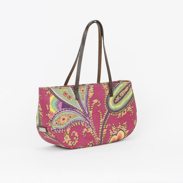 Fuchsia paisley tote by Etro with yellow, purple, green, and orange accent colors and brown leather dual handles.