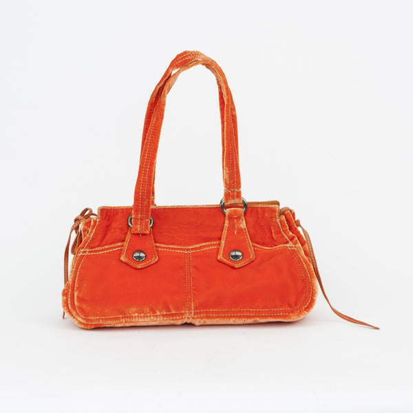 Prada neon orange velvet handbag with two pockets on each side with snap closures, side gathers with leather ties, and dual handles.