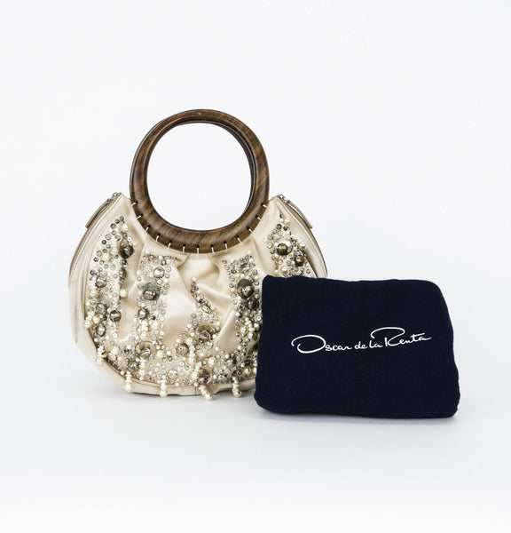 Oscar De La Renta champagne colored satin cocktail handbag with pearl, bead, rhinestone, brass embellishments & dual wooden handles With Dust Bag