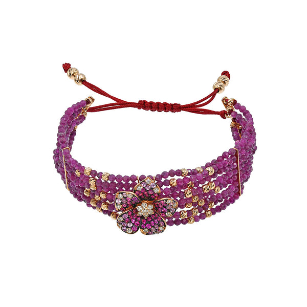 18K Gold bracelet with diamonds and rubies. Thje flower is surrounded by ruby and gold beads.