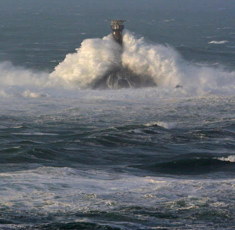 Longships Lighthouse hugged by a huge wave, Cornwall