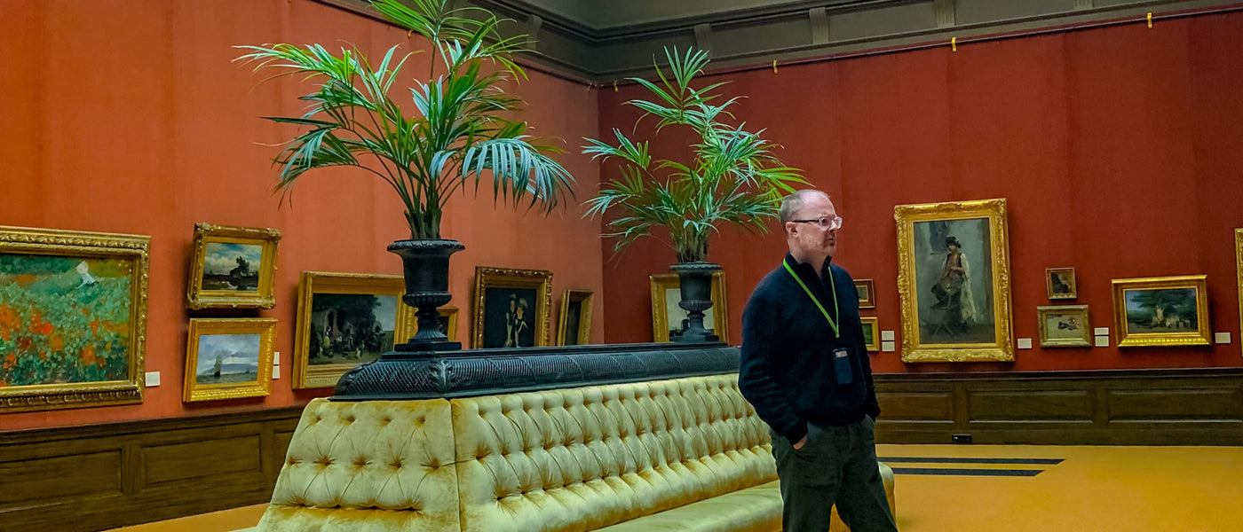 Photo of Christopher St.Leger in an art gallery looking at impressionist paintings. Gallery has terra-cotta red walls, a large tufted yellow sofa with palm plants behind it. All of the paintings have ornate gold frames.