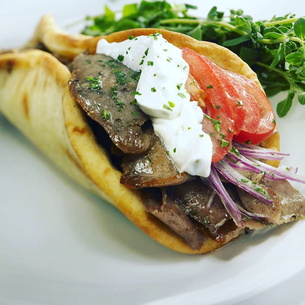 Mediterranean gyro with red onions, tomato, and tesiki sauce
