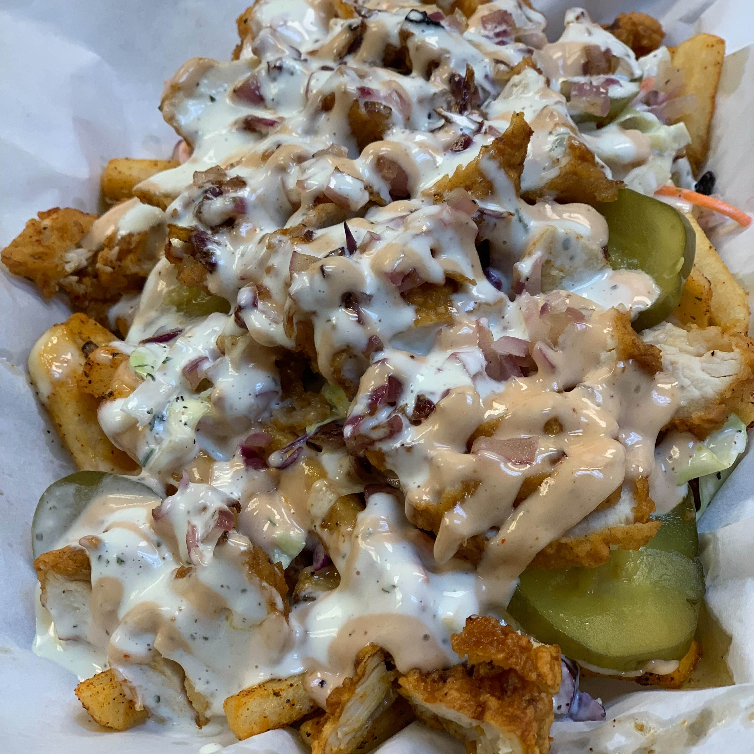 Bun Bun Fries loaded with grilled onion, fried chicken, coleslaw and pickless,