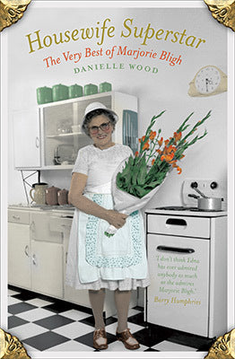 Senior woman in kitchen with bunch of gladioli.