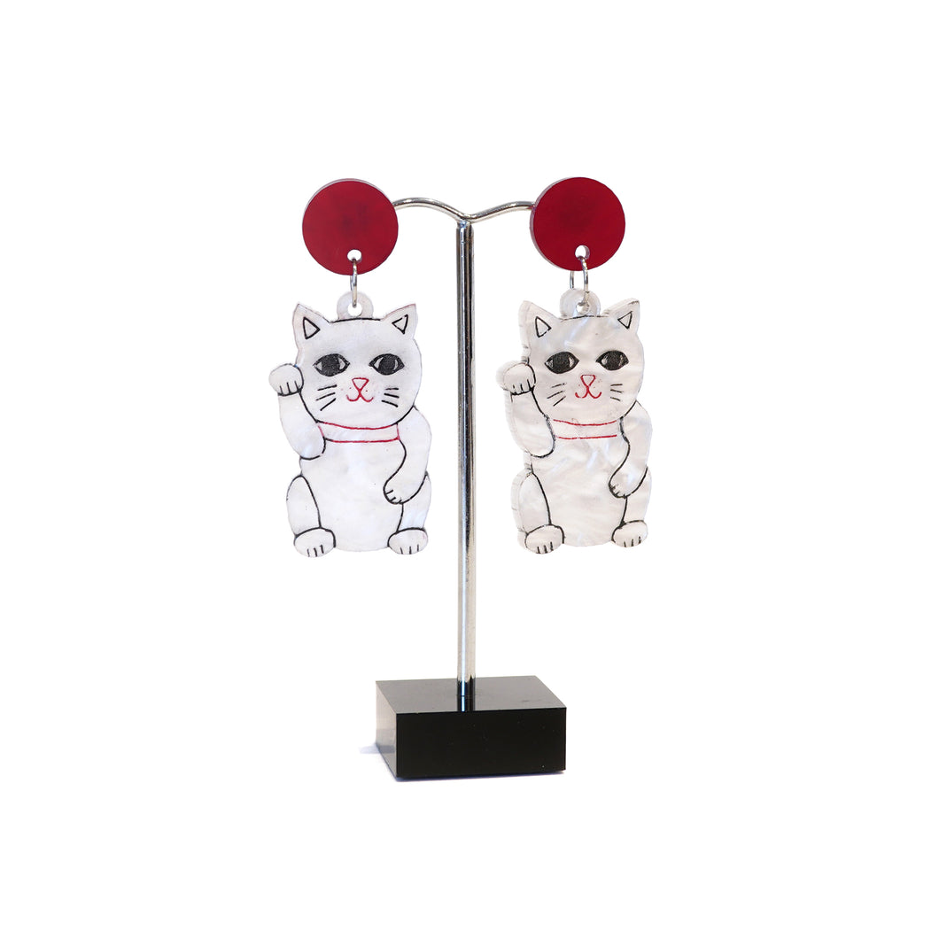 White lucky cats with red disc stud earrings.