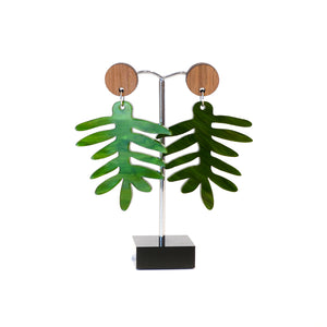 Green acrylic leaf earrings with wooden disc stud fitting.
