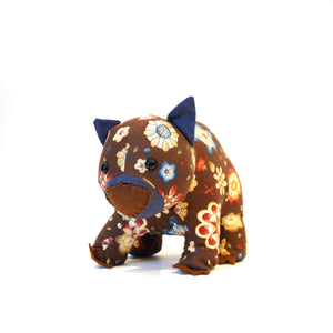 Handmade wombat with flower patterned fabric on brown background