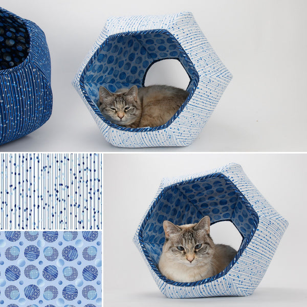 Our small cat model named Tink is inside a Cat Ball cat bed made in white, blue and metallic fabric