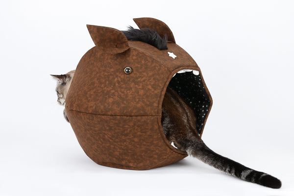 A cat sits with his head and tail sticking out of the novelty horse design Cat Ball® cat bed