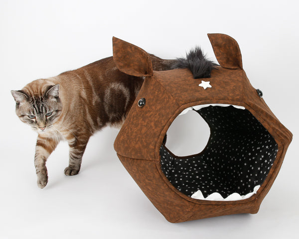 A cat walking around the novelty horse Cat Ball cat bed