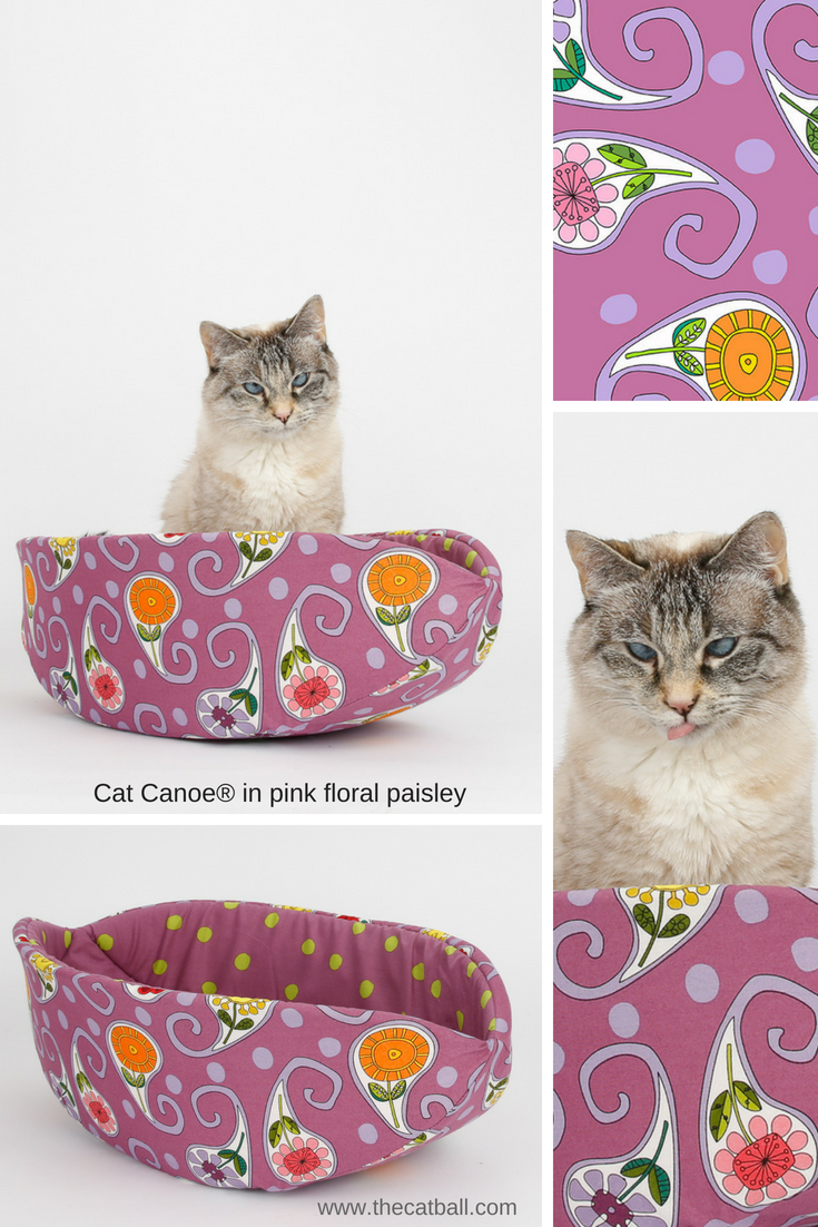 A small cross eyed cat sits in a Cat Canoe modern cat bed made in a pink floral paisley fabric
