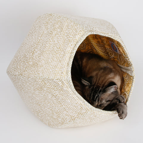 The Cat Ball® cat bed made with shiny metallic gold ink on a white background and a coordinating paisley lining. These fabrics are 100% cotton. This hexagonal cat bed is fully lined and has an opening on each end. Made in USA.
