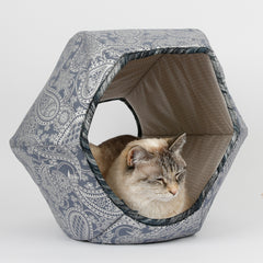 The Cat Ball® cat bed made in an ornate paisley print, silver metallic ink on a steel blue background. This hexagonal cat bed is fully lined and has an opening on each end. Made in USA.