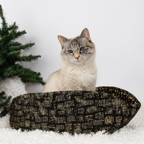 "Cat Canoe modern cat bed made in a black cotton fabric with an abstracted ""gold bricks"" design."