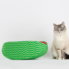 Cat Canoe® modern cat bed made in a green zig zag fabric to look like a slice of watermelon. The reluctant model here is Tink, who expects to be fed before participating.