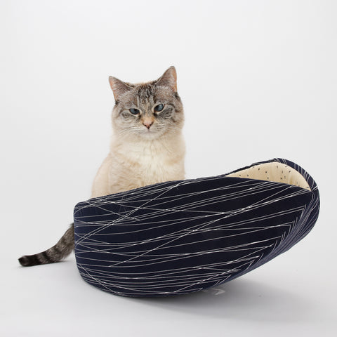 The Cat Canoe is a modern cat bed, made in an abstracted neutral navy print and lined with a tan typography print