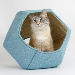 The Cat Ball cat bed is a hexagonal cat bed with two openings, one larger than the other. Shown here in robin egg blue. Made in USA