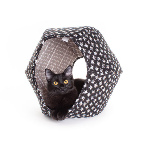 A black cat relaxing in the Cat Ball® modern cat bed, made in skull and crossbones cotton fabric