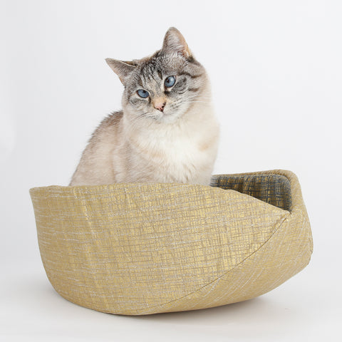 The Cat Canoe is a modern cat bed, made in a monochromatic gold metallic fabric with a navy and gold lining.