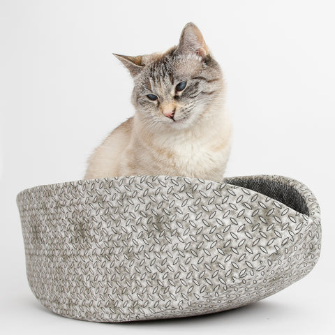 A cat inside the Cat Canoe, a modern pet bed made of fabric and foam