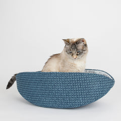 A small lynx point cat sits inside Cat Canoe modern cat bed, made in teal color cotton fabrics