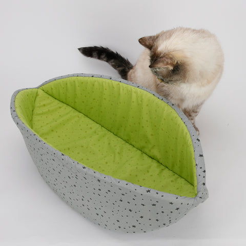 Tink, the smallest cat model for The Cat Ball, LLC, poses next to a Cat Canoe bed made in contrasting grey and lime green fabrics