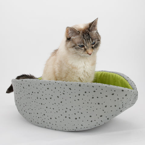 Tink, the smallest cat model for The Cat Ball, LLC, sits in a Cat Canoe bed made in contrasting grey and lime green fabrics