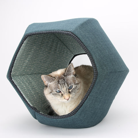 The Cat Ball® cat bed is hexagonal cat furniture with two openings. Your cat can get inside this pod-style cat bed and then look out through the two openings.
