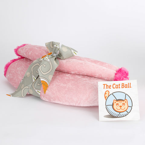 The Cat Ball is a modern cat bed, made here in baby pink velvet, with soft fur trimmed openings and lined with a grey and multi floral paisley fabric in cotton. This pod style cat bed is made in the USA.