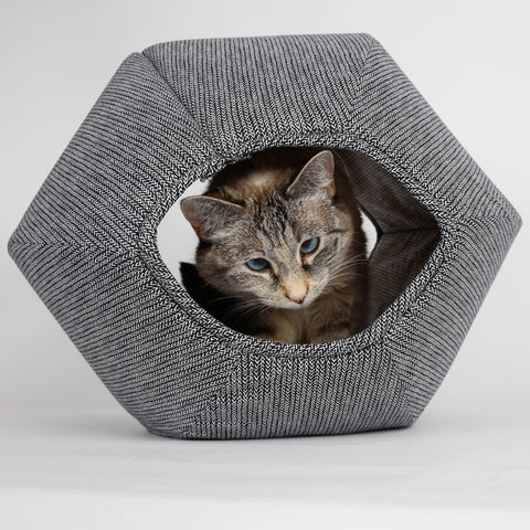 A small cat peeks out of the Cat Ball cat bed made in black and white fabrics. The Cat Ball is made in the USA