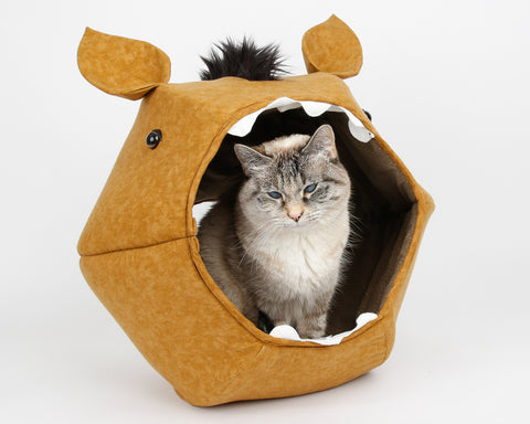 A cat sitting inside a prototype novelty horse Cat Ball cat bed