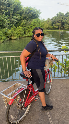 Aura of Opulence's CEO poses with a bike in Hermann Park, Houston, TX