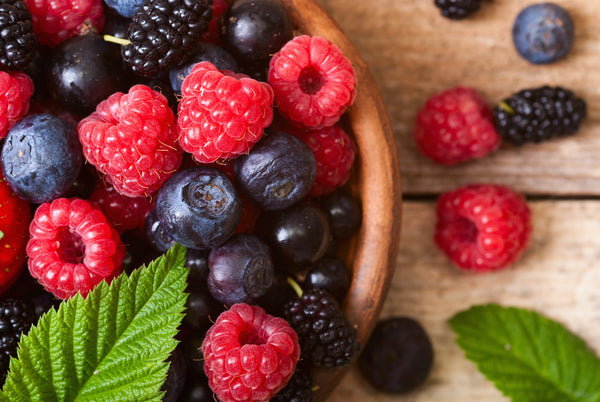 Berries in wooden bowl garnished with mint
