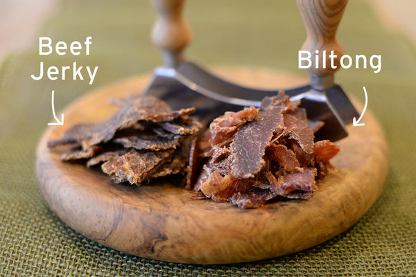 Beef Jerky and biltong on wood table with knife.