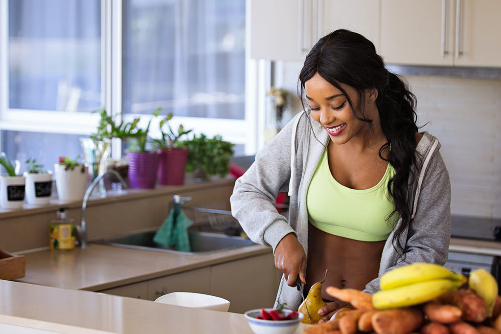 Healthy woman cutting up fruit for a balanced snack.