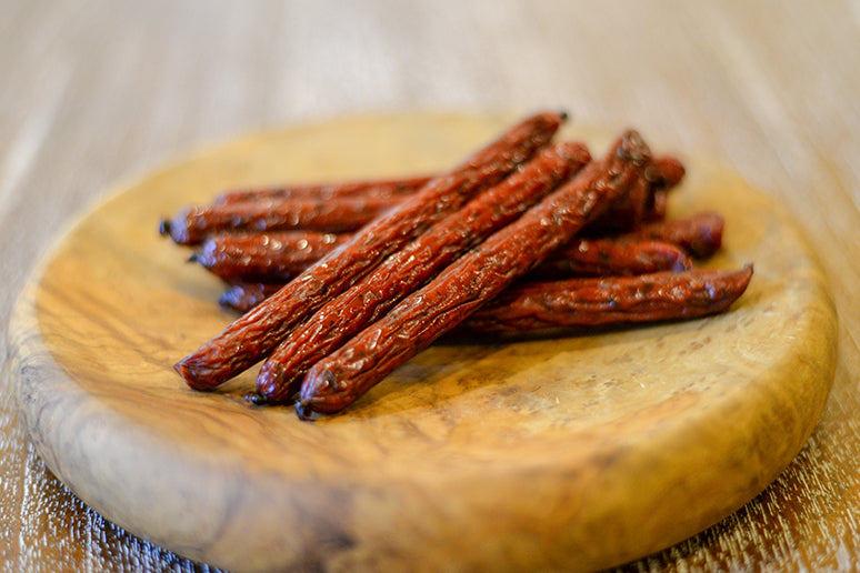 Beef sticks on a table in a bowl.